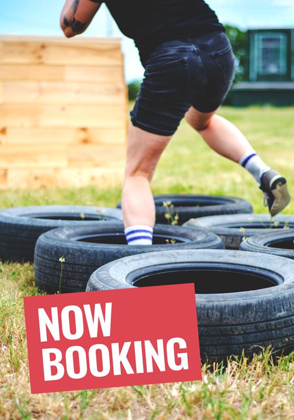 Image Description: a photograhp of a person running through tires as part of an agility course with a red overlay saying Now Booking.